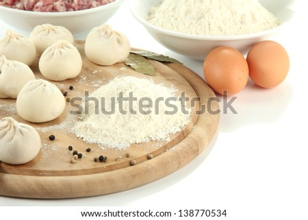 Raw Georgian khinkali on wooden desk and ingredients, isolated on white