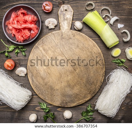raw glass noodles, soy sauce, parsley, cherry tomatoes, onions, lettuce, mushrooms on a cutting board on wooden rustic background top view close up - stock photo