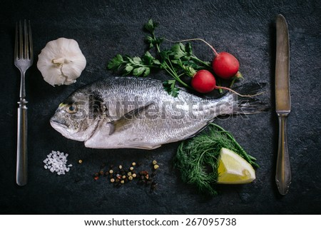 Raw glithead fish with ingredients from above on dark background - stock photo
