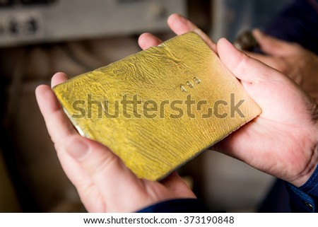 Raw gold ingot in the hands - stock photo