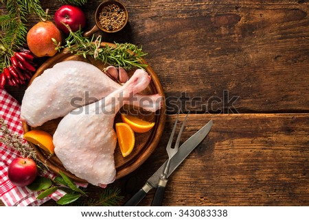 Raw goose legs with herbs on cutting board. Cooking at Christmas time - stock photo