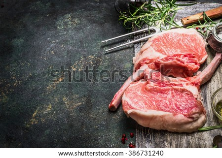 Raw gourmet pork cutlet for grill, barbecue or cooking with herbs ,spices and meat fork on dark rustic background. Porco Iberico French Racks. Meat food. Pork rib chop with bone. - stock photo