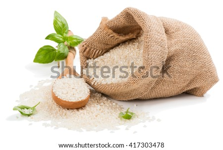 Raw grain white rice grains in burlap bag decorated with green basil isolated on white background.