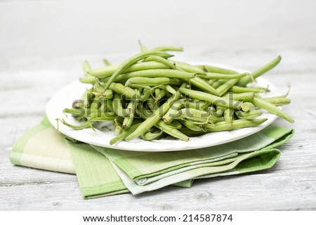 Raw green beans on plate - stock photo