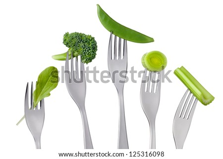raw green vegetables selection on forks isolated against white background