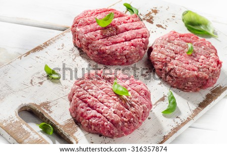 Raw Ground beef Burger steak patties on a wooden cutting board. Top view - stock photo