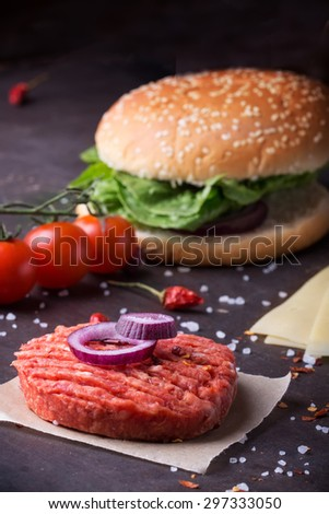 Raw Ground beef meat Burger steak cutlets with seasoning, buns, cheese, tomatoes, onion rings and salad on  black background, - stock photo