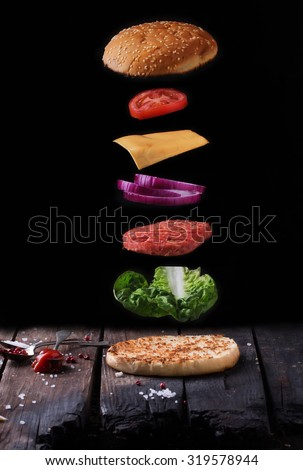 Raw Ground beef meat Burger steak cutlets with seasoning, cheese, tomatoes, salad and bun  flying over  vintage wooden board, black background - stock photo
