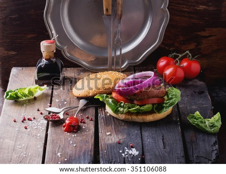 Raw Ground beef meat Burger steak cutlets with seasoning, cheese, tomatoes, salad and bun on vintage wooden boards, black background - stock photo