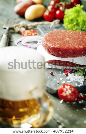 Raw Ground beef meat Burger steak cutlets with seasoning,vegetables and beer on vintage wooden boards - stock photo