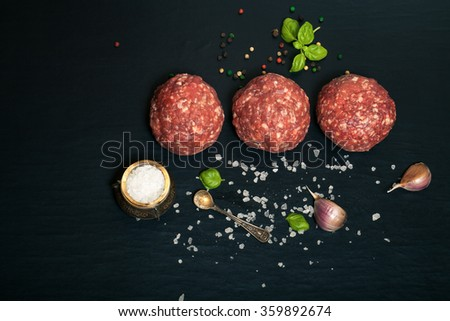 Raw ground beef meat steak cutlets with herbs and spices on black table or board for background. Selective focus. Toned. - stock photo
