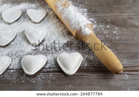 Raw heart shaped dumplings, flour and rolling pin on wooden background. Cooking ravioli. Shallow depth of field. - stock photo