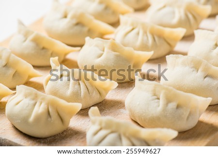 Raw Homemade Chinese Dumplings on Wooden Board