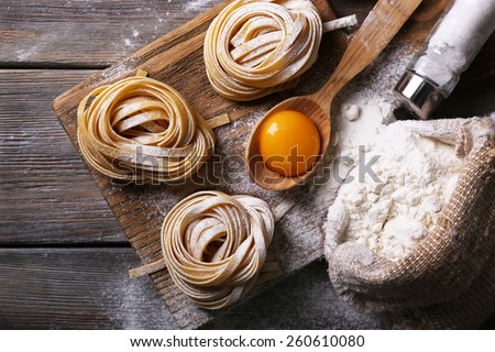 Raw homemade pasta and ingredients for pasta on wooden background - stock photo