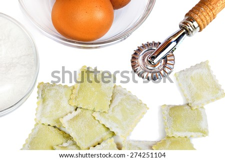raw homemade ravioli with eggs and pastry wheel over white - stock photo