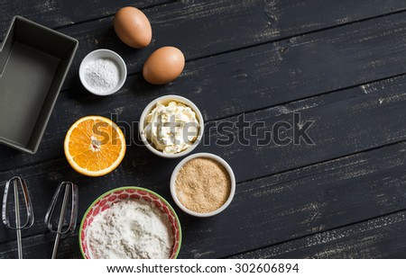 raw ingredients - flour, eggs, butter, sugar, orange - to cook orange cake. Ingredients for baking. Ingredients for the dough. On a dark wooden surface - stock photo