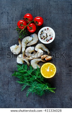Raw ingredients for preparing fresh seafood with shrimp, tomatoes, fresh herbs and spices on dark vintage background, top view. - stock photo