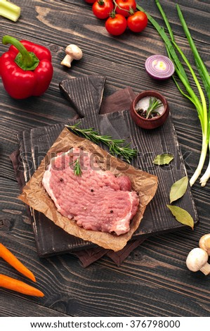 Raw ingredients for the preparation tasty and healthy food - raw juicy piece of meat with green onions, bulb onion, peppers, carrots, mushrooms and rosemary. top view - stock photo