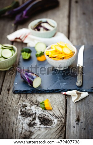 Raw ingredients for traditional French casserole, ratatouille: zucchini, red bell pepper, yellow squash, eggplant sliced on cutting board. Also available in horizontal format.