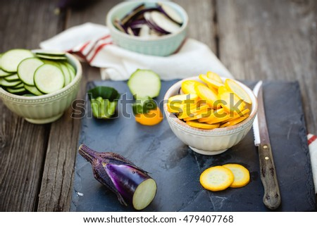 Raw ingredients for traditional French casserole, ratatouille: zucchini, red bell pepper, yellow squash, eggplant sliced on cutting board. Also available in vertical format.