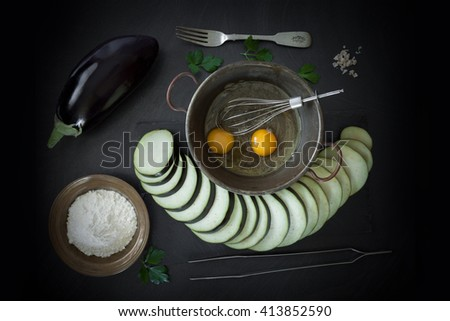 Raw ingredients necessary for fried eggplant recipe: eggs, flour, salt and eggplants. Top view shot. - stock photo