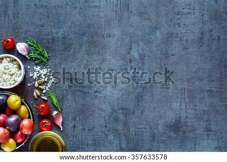 Raw ingredients (potatoes, tomatoes, garlic and olive oil) over dark grunge background with space for text. Top view. Fresh organic vegetables from garden for healthy cooking. - stock photo