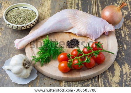 Raw ingredients: turkey leg, tomatoes, fresh dill, black peppers, onion, garlic and dried oregano on a wooden board. - stock photo