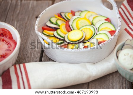 Raw ingredients zucchini, bell pepper, onion, eggplant, tomato sauce in gratin dish for traditional French ratatouille. Close up. Also available in vertical format.