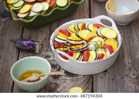 Raw ingredients zucchini, bell pepper, onion, eggplant, tomato sauce in gratin dish for traditional French ratatouille. Also available in vertical format.