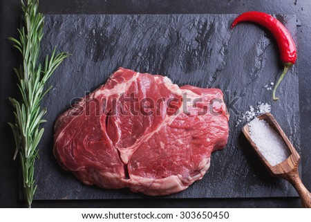 Raw Irish Sirloin Beef Steak on a slate stone board ready to be roasted with rosemary, chili pepper and salt - stock photo