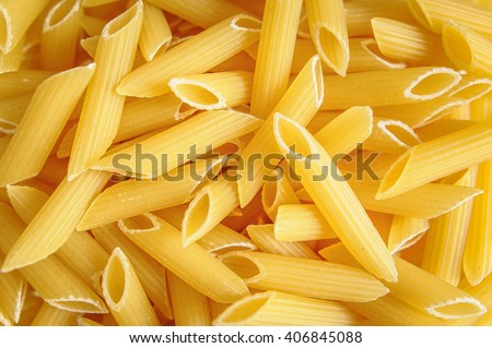 Raw italian penne pasta cooking ingredient texture as background image