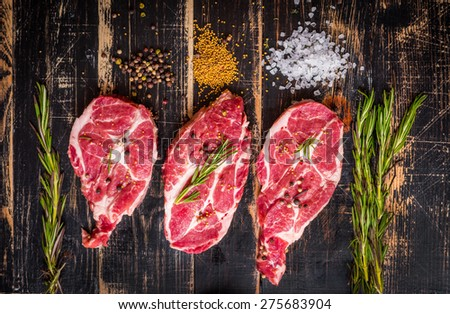 Raw juicy meat steak on dark wooden background - stock photo