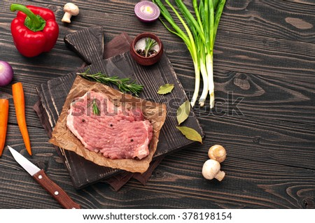 Raw juicy piece of meat with green onions, bulb onion, peppers, carrots, mushrooms and rosemary. Raw ingredients for the preparation tasty and healthy food, top view with copy space - stock photo
