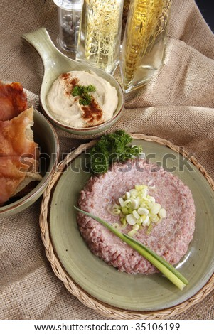Raw kibbe, fried pitta bread, hummus tahine and seasoned olive oils - stock photo