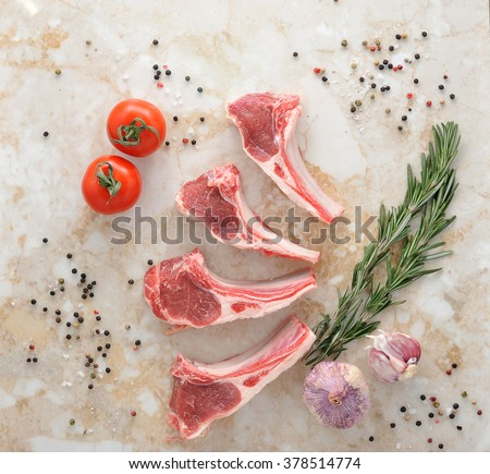 Raw lamb chops. Rack of Lamb with rosemary,  young garlic and spices on marble background, top view - stock photo