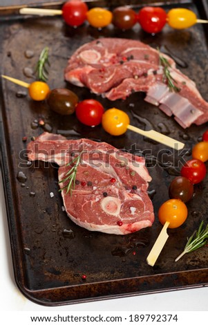 Raw lamb chops with cherry tomato and rosemary herb ready to cook. Selective focus.