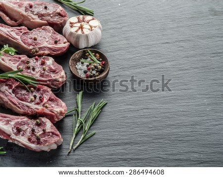 Raw lamb chops with garlic and herbs on the old wooden table. - stock photo