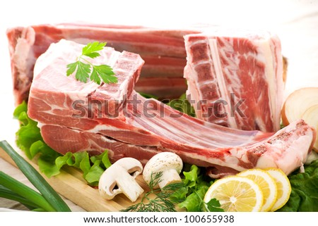Raw Lamb ribs arranged with mushrooms, lemon, parsley, and lettuce on a cutting bord - stock photo