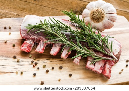 Raw lamb ribs with rosemary, pepper and garlic on wooden board. - stock photo