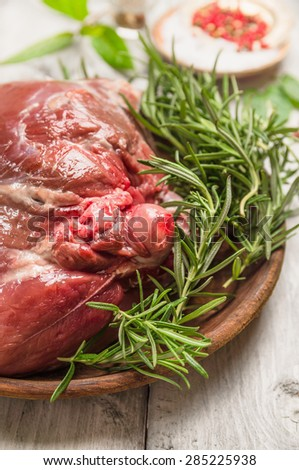 Raw leg of lamb , preparation on rustic wooden background - stock photo