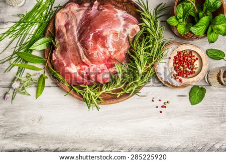 Raw leg of lamb with fresh herb on white rustic wooden background, top view, place for text,frame - stock photo