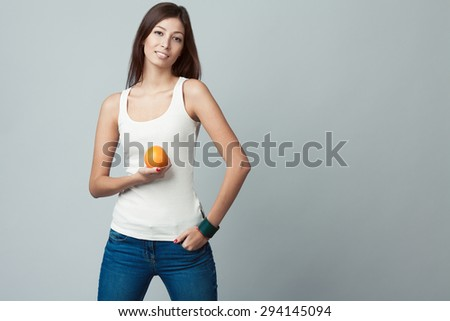 Raw, living food concept. Portrait of happy young woman wearing white sleeveless shirt, jeans, holding orange over gray background. Casual clothing. Fit body. Natural make-up. Copy-space. Studio shot - stock photo