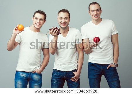 Raw, living food, veggie concept. Portrait of three happy young men wearing white t-shirts, blue jeans, holding fruits in hands over gray background. Casual clothing. Muscular bodies. Studio shot - stock photo