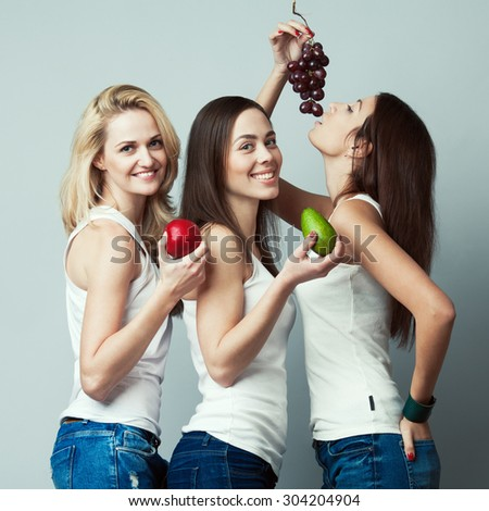 Raw, living food, veggie concept. Portrait of three happy young women wearing white sleeveless shirts, holding fruits over gray background. Casual clothing. Perfect skin, natural make-up. Studio shot