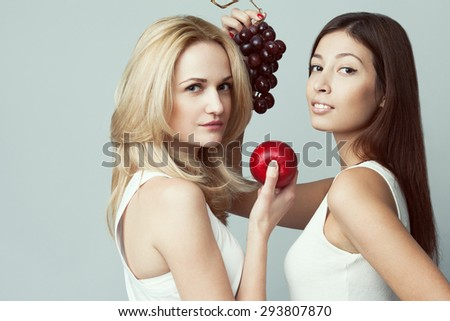 Raw, living food, veggie concept. Portrait of two happy young women wearing white sleeveless shirts, holding fruits over gray background. Casual clothing. Perfect skin, natural make-up. Copy-space - stock photo