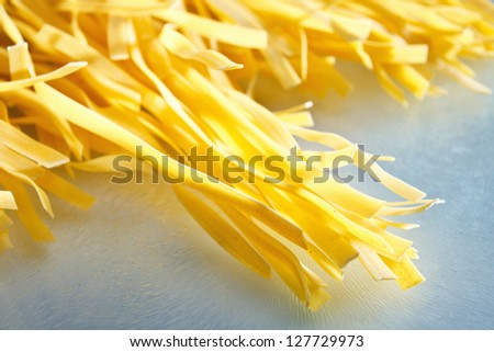 Raw, long tagliatelle pasta on a glass plate
