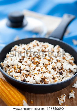 Raw maize and popcorn in a frying pan, closeup - stock photo