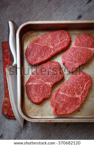 Raw marbled beef steak in a pan - stock photo