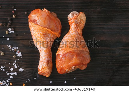Raw Marinated chicken meat legs for BBQ with seasoning salt and pepper over dark wooden background. Top view with copy space. - stock photo