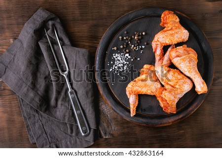 Raw Marinated chicken meat wings and legs for BBQ, served on round wood chopping board with seasoning and vintage meat fork on textile over dark wooden background. Top view with copy space. - stock photo